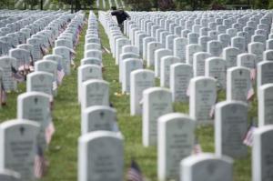 A man pauses at a grave during Memorial Day celebrations at Arlington National Cemetery in Arlington, Virginia May 25, 2015. REUTERS/Joshua Roberts